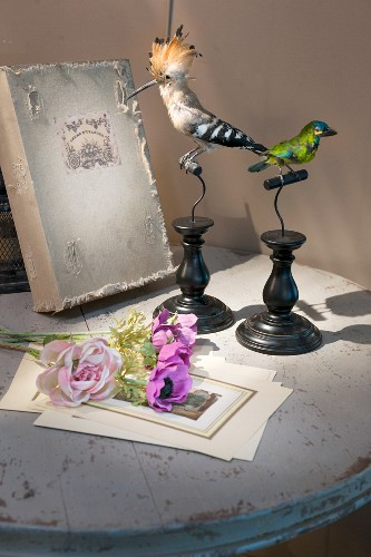 Vintage-style arrangement of book, stuffed birds and flowers on table