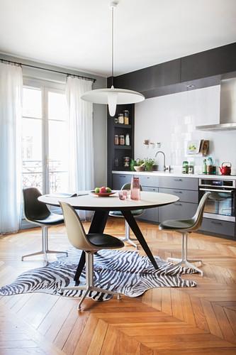 Runder Esstisch mit Retrostühlen auf Zebrafell in grauer Einbauküche