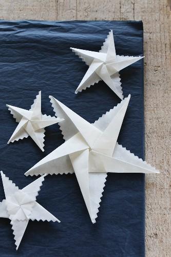 Folded white paper stars with zig-zag edges