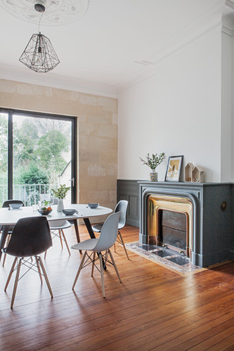 Dining table and chairs in front of fireplace and terrace doors