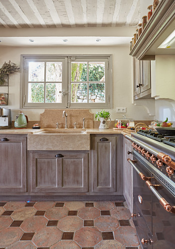 L-shaped country-house kitchen counter with terracotta floor tiles