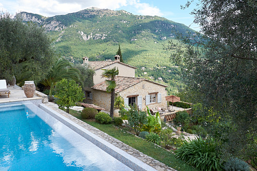 View of pool, stone house and mountain landscape