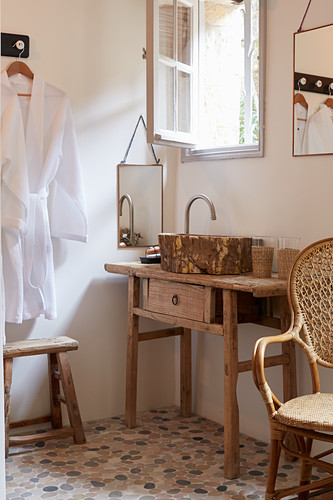 Rustic wooden table with countertop sink below lattice window, white dressing gown on wall in simple bathroom