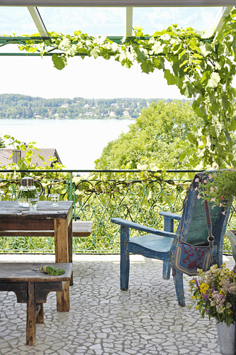 Rustic wooden furniture on balcony with view of lake