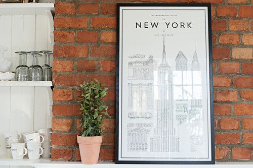 Picture of New York on brick wall next to shelving