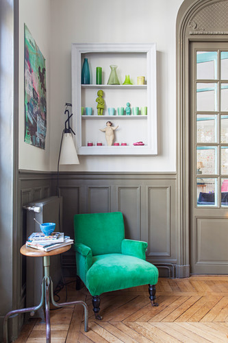 Emerald velvet armchair against grey wainscoting and below wall-mounted display case