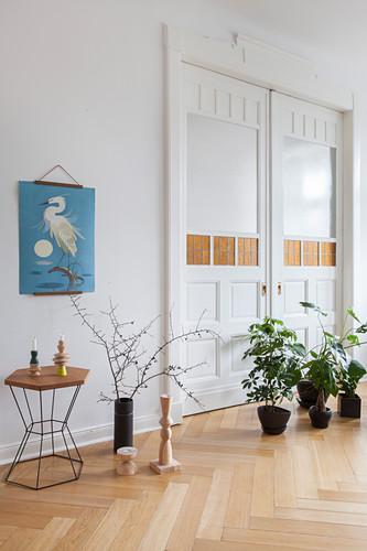Zimmerpflanzen auf dem Boden vor geschlossener Flügeltür in Altbauwohnung