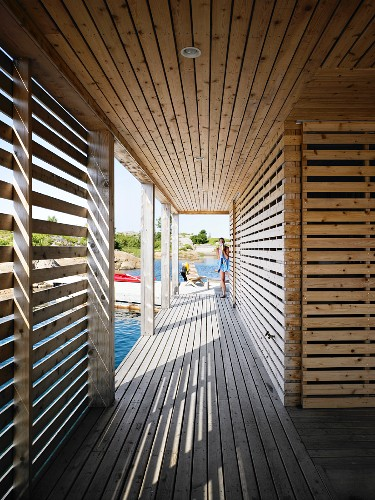 Slatted wooden arcade surrounding floating wooden house; pattern of light and shade