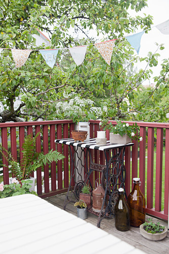 Bunting above old sewing-machine table on balcony