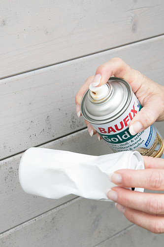Spraying crumpled drinks can with gold paint