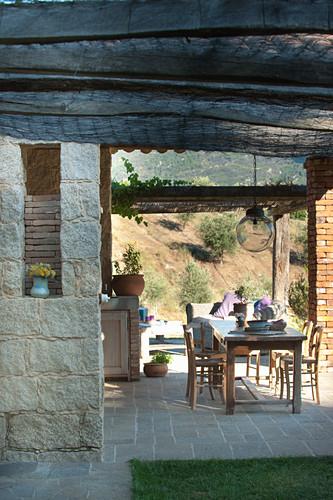 Holztisch auf überdachter Terrasse im mediterranen Garten