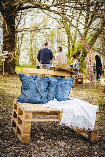 Cushions made from old jeans on chair built from pallets in garden