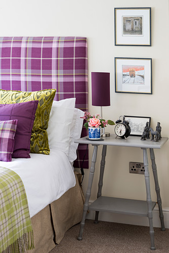 Grey bedside table next to bed with purple tartan headboard