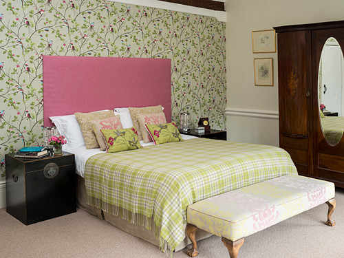 Floral wallpaper in romantic bedroom in shades of green and pink