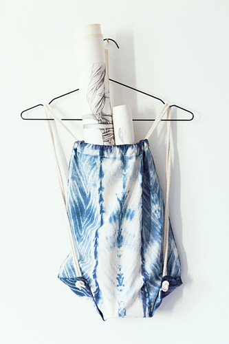 Sports bag hand-dyed with Shibori pattern hung from wire coathanger