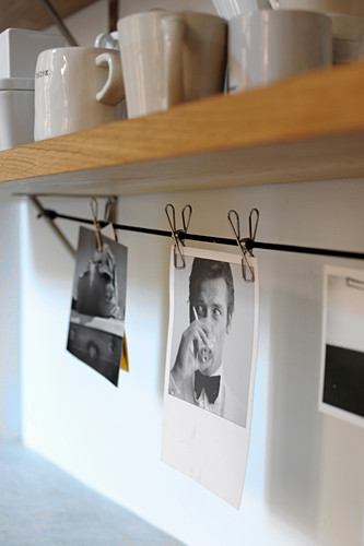 Black and white photos clipped to cord below crockery on shelf with clothes pegs