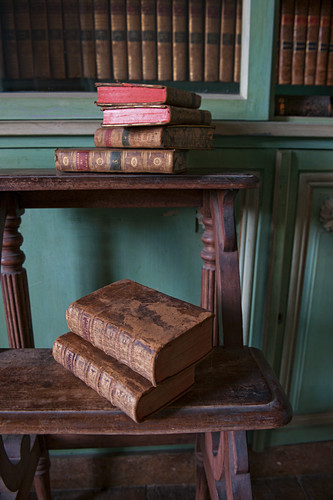 Antiquarian books on old wooden steps in front of bookcase