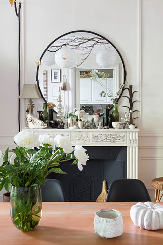 Vase of flowers on dining table in front of lavishly decorated mantelpiece