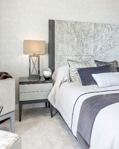 Bedside lamp on cabinet next to bed with tall headboard in elegant bedroom in shades of grey