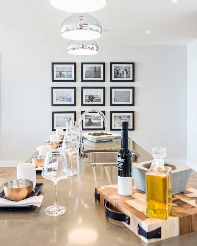 Langer, glänzender Esstisch mit Gedecken, im Hintergrund Bildergalerie an der Wand
