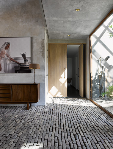Table lamp on retro sideboard below photo on wall in foyer with concrete walls