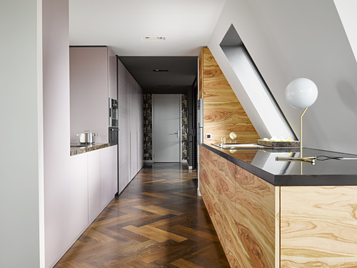 Minimalist kitchen with wooden fronts under sloping ceiling