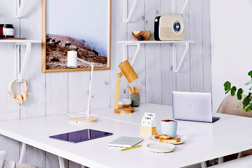 White desks and wall brackets on plank wall