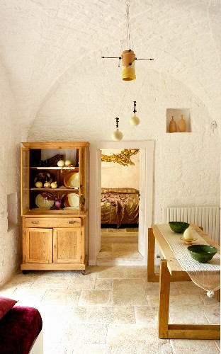 Wooden table and dresser against whitewashed walls in renovated trullo