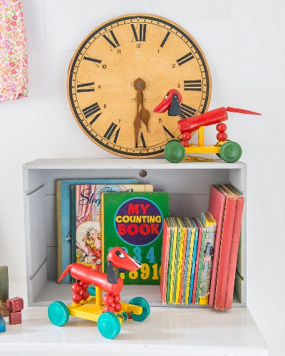 Vintage toy clock with Roman numerals, retro toys and colourful children's books