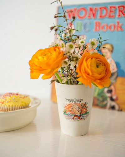 Orange ranunculus and white flowers in retro beaker with printed picture and motto