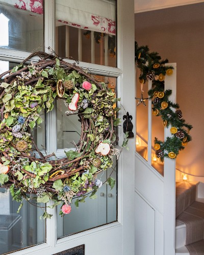 Wreath with dried apple slices on front door and garland with slices of oranges on handrail of staircase