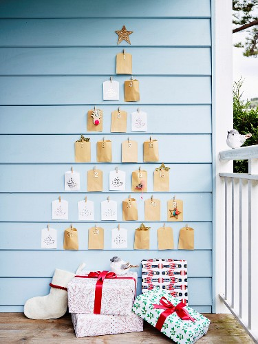 Advent calendar made of paper bags in Christmas tree shape on the wall