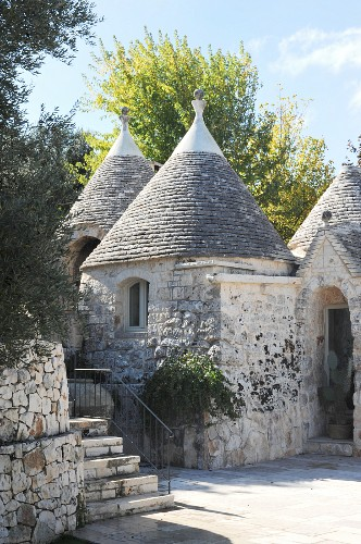 Traditional trullo houses below blue sky