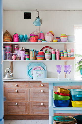 Colourful crockery on wall-mounted shelves above wooden cupboards in kitchen