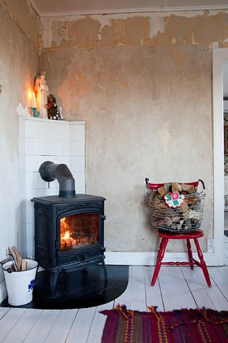Fire in log burner in corner against stripped plaster walls