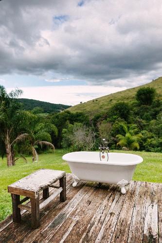 Vintage Badewanne mit Klauenfüßen und Holzbank auf Holzdeck vor Hügellandschaft, Reserva do Ibitipoca, Brasilien