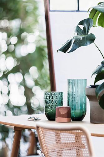 Grüne Vasen mit Relief und Monsterapflanze auf dem Tisch