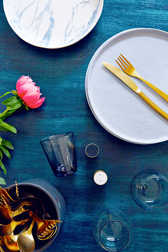 Gold cutlery on plate, glasses, salt and pepper shakers and flowers on table