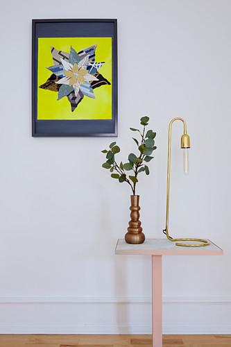 Vase mit Blätterzweig und Leselampe auf Beistelltisch, darüber buntes Bild