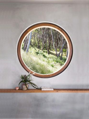 Rundes Fenster mit Blick in den Wald in grauer Wand mit Regal