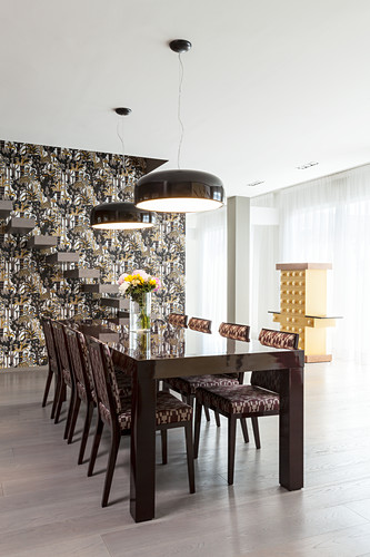 Dining table and upholstered chairs in front of cantilever stairs on wall with patterned wallpaper