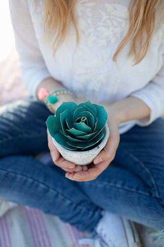 Frau hält Blumentöpfchen mit gebastelter Sukkulente aus Papier