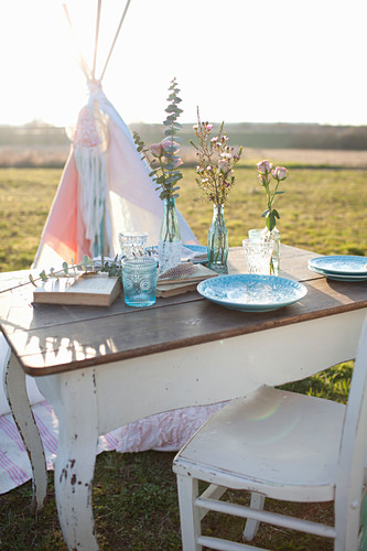 Romantically set table in front of teepee in meadow