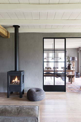 Fire in wood-burning stove against grey wall with door leading into dining room