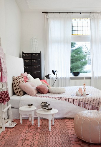 Small white tables, leather pouffe and fringed blanket on bed in feminine bedroom
