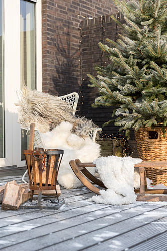Comfortable seating area and brazier on wintry terrace