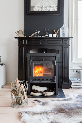 Cast iron log burner in black fire surround against black chimney breast