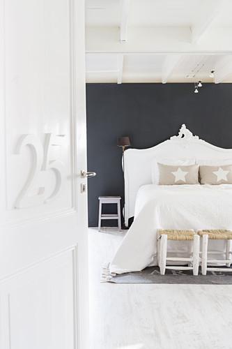 Offene Tür mit Nummer zum weißen Schlafzimmer mit schwarzer Wand