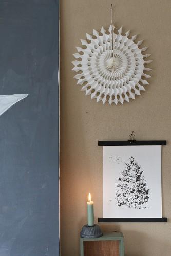 Festive arrangement of picture, paper sunburst and lit candle against wall