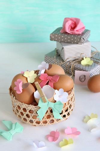 Ausgepustete Eier dekoriert mit Papierblumen und Papierschleife in Osterkörbchen